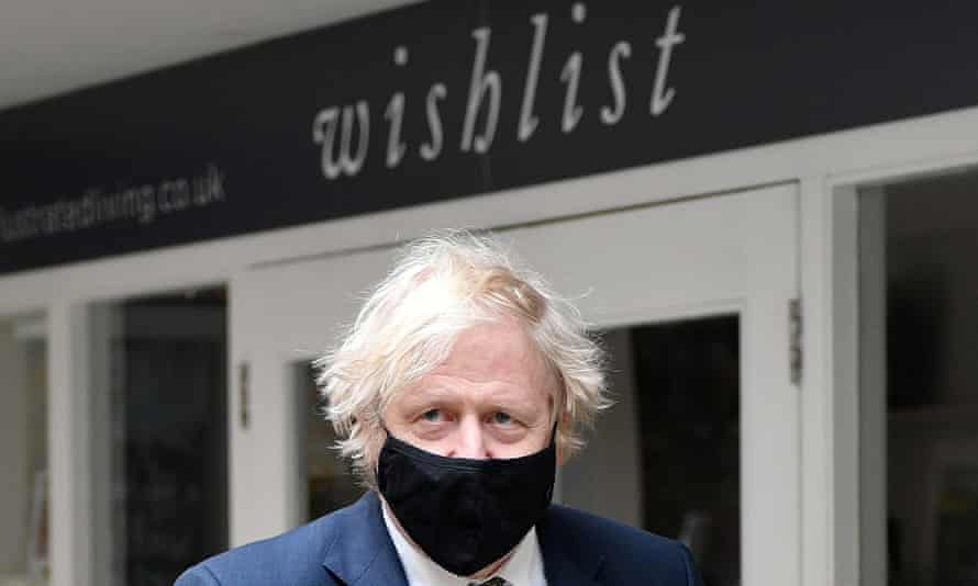 Boris Johnson in a mask standing outside a business whose sign reads 'wishlist'