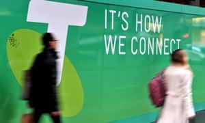 Commuters pass a Telstra sign