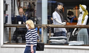 A customer sits with his laptop beside display mannequins at a cafe in Essen last month