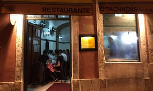 Exterior shot, at night, of an illuminated Restaurante O Tachadas, Santos, Lison, Portugal.