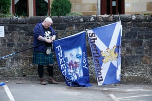 A man in a kilt stands in a street as he gets ready to attend the All Under One Banner march