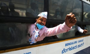 Bangalore, India. A detained protester shouts slogans from a police bus during a rally against the introduction of new agri-ordinances.