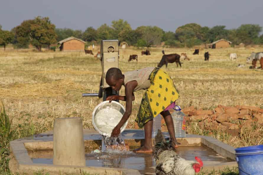 A girl washes dishes at a borehole near Eland coal mine in Mwabulambo, Karonga district