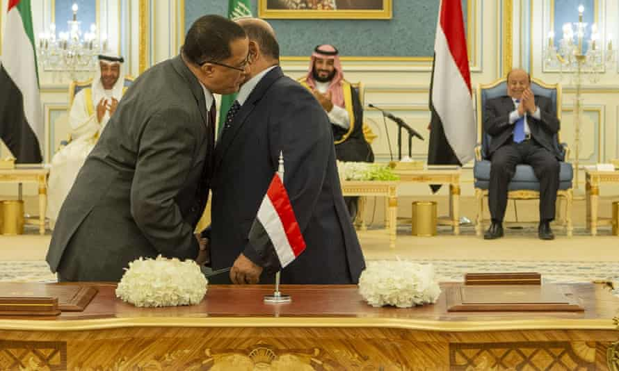 Yemen's deputy prime minister Ahmed Saeed al-Khanbashi (R) and the Southern Transitional Council representative Nasser al-Khabji shake hands during the signing ceremony.