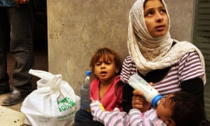 A woman from the Syrian city of Idlib begs with her two children in a wealthy district of Beirut in November 2013