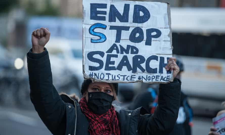 A demonstrator holds a placard at a protest against the misuse of stop and search powers in London
