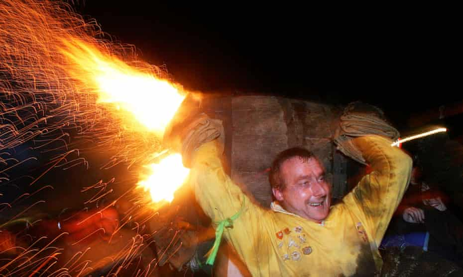 A man runs while carrying a burning barrel soaked in tar during the annual event in Ottery St Mary, Devon.