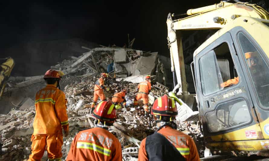 Rescuers search through the rubble following the building collapse in Wenzhou