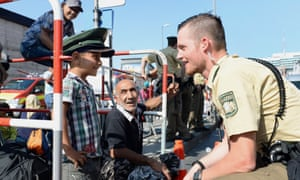 A German police officer talks to a young refugee as he waits for a bus outside the central railway station in Munich.