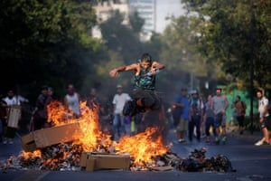 Santiago, Chile: a man wearing rollerblades jumps over a burning barricade during anti-government protests in Providencia