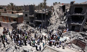 Libyans gather on June 19, 2011 next to the rubble of buildings the Libyan authorities said were damaged by airstrikes on Tripoli's residential district of Arada