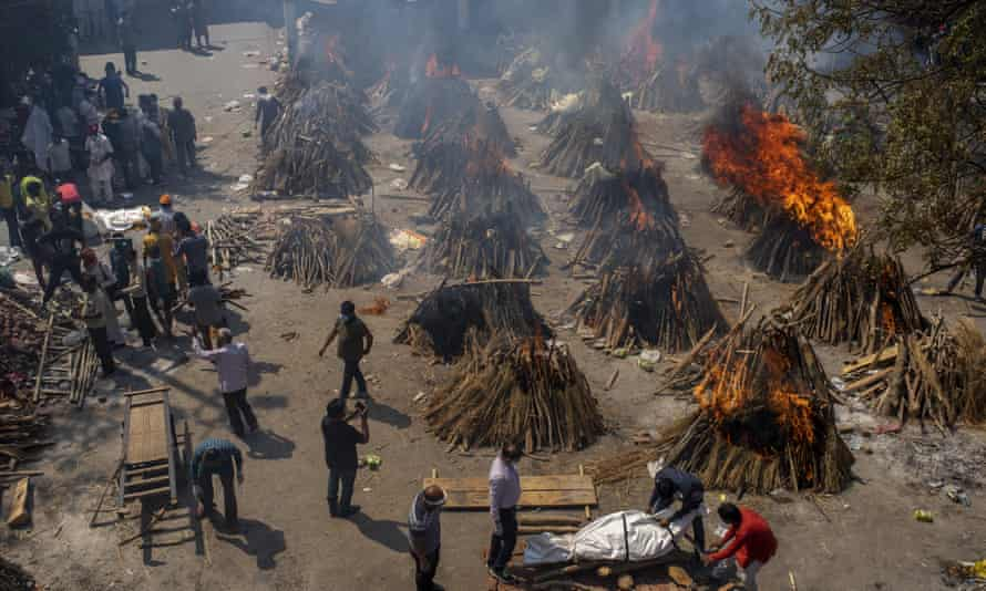 Rows of roughly conical wooden pyres on an area of flat ground, some alight, some not, being attended to by staff, photographed from above