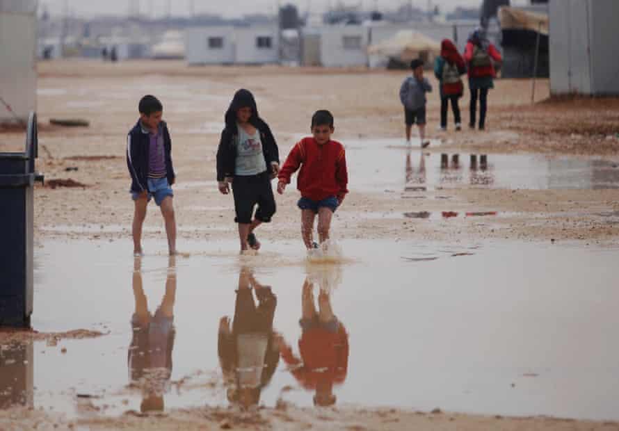 Syrian children walk through the Zaatari refugee camp.