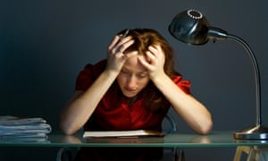 A stressed businesswoman with head in hands leaning on desk