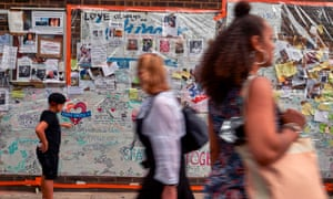 A boy looks at messages left by well-wishers in tribute to the victims of the Grenfell Tower fire.