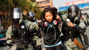 A protester is detained by riot police while attempting to leave the campus of Hong Kong Polytechnic University.