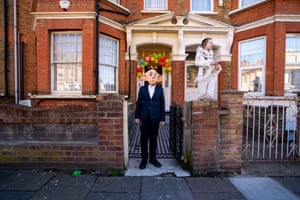 London, UK. Children celebrating the Jewish holiday Purim stand in front of their house waiting for guests
