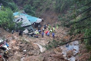 Rescuers search for three missing people who were buried by a landslide at Balacbac in the Philippines