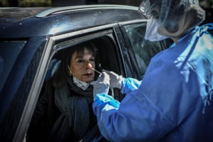 Paris, FranceA nurse collects a sample from a woman at a COVID-19 screening station outside the district hall of the 17th arrondissement.