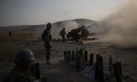 Kurdish Peshmerga soldiers fire artillery at Islamic State positions in Bashiqa.