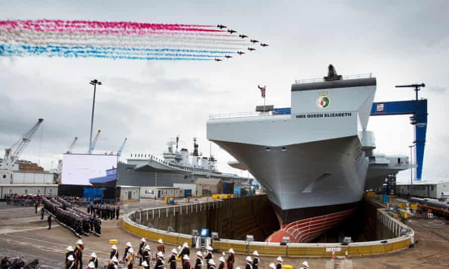 The Queen names the largest warship built in the UK - at nearly double the original estimate - at a ceremony in Fife's Rosyth dockyard.