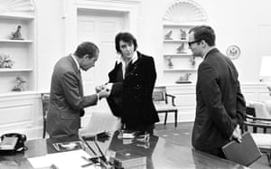 Nixon gets a close look at Elvis's get-up, watched by White House aide Egil Krogh.