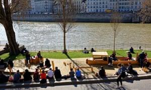 People sit by the river on a sunny day, Parc Rives de Seine, Paris, France.
