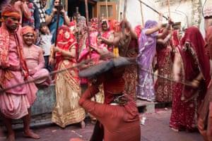 Indian women beat men with sticks (lathi).