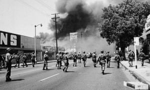 Armed National Guardsmen march toward smoke during street fires of the Watts riots, Los Angeles, California, August 1965.