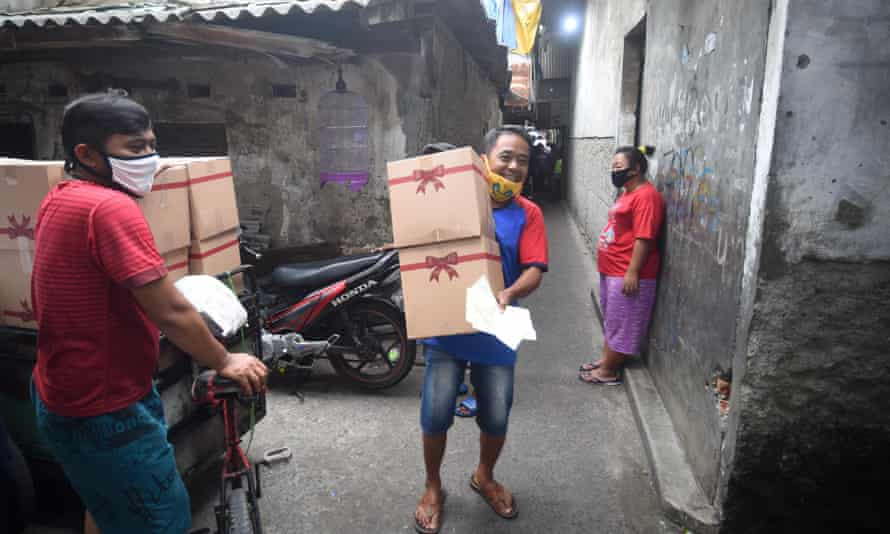 A Jakarta resident carries packages assistance for poor family ahead of large-scale social restriction implementation.
