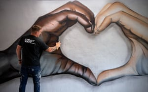Peterborough, UK Black and white hands join to make a heart shape in this skilfully spray painted mural by Nath Murdoch, seen here adding a finishing touch. It's tempting to wonder if he is taking too cosy and optimistic a multi-racial message from an incident that has revealed the depth of casually violent racial injustice that divides America. But there's nothing wrong with a bit of hope on our streets.