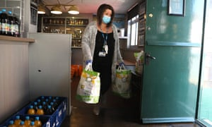 An NHS mental health worker collects food from a food bank set up in a pub in Northampton.