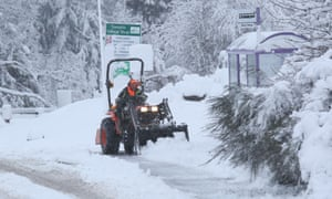 A man clearing snow in Tomatin near Inverness in Scotland