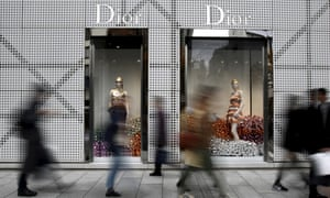 People walk past a Dior store