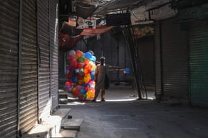 Lahore, Pakistan: a balloon vendor walks past a shuttered market in Lahore, during a Covid lockdown