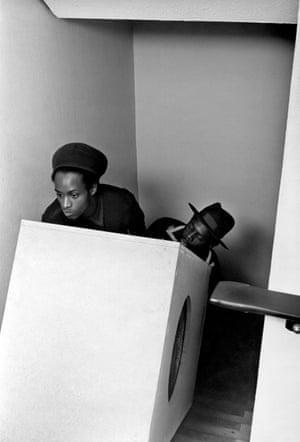 Two men haul a speaker cabinet up a flight of stairs in Stonebridge, London, 1983.