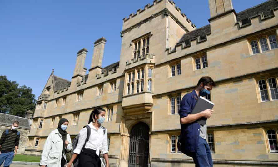 People in masks walk past Wadham college Oxford
