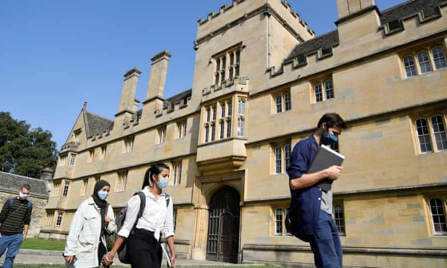 People wearing face masks walk past Wadham College, Oxford University, ahead of the new academic year.