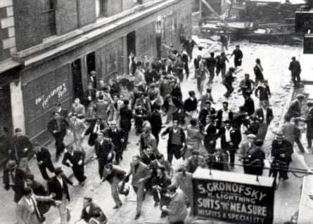'Battle of Cable Street', Aldgate, London, 5th October 1936. An anti-Fascist crowd, some of them carrying missiles, run from a barricade they have erected near Aldgate. The police are charging on the far side of the barricade, which has been reinforced with paving stones.