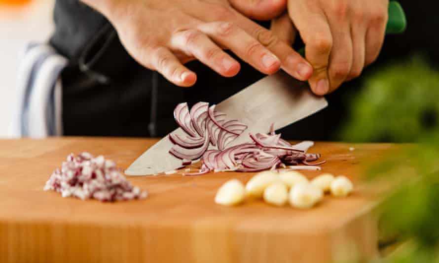 A person chopping red onion on a wooden cutting board.