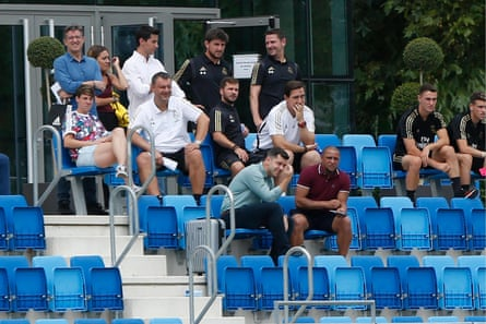 Former Real Madrid player Roberto Carlos (bottom row, right) and current Real Madrid players and staff watch Tacón's friendly against Sevilla.
