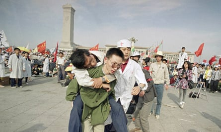 Medics rush a student hunger striker from Tiananmen Square after he collapsed during the protest in May 1989