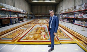 Mobilier National's Hervé Lemoine poses in front of a damaged Notre Dame Cathedral carpet