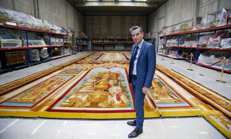 Mobilier National's Hervé Lemoine poses in front of a damaged Notre Dame Cathedral carpet
