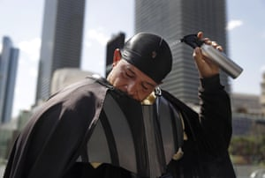 Chris Mitchell pours water over his head to cool off in a Darth Vader costume along the Las Vegas Strip, where he takes photographs with tourists