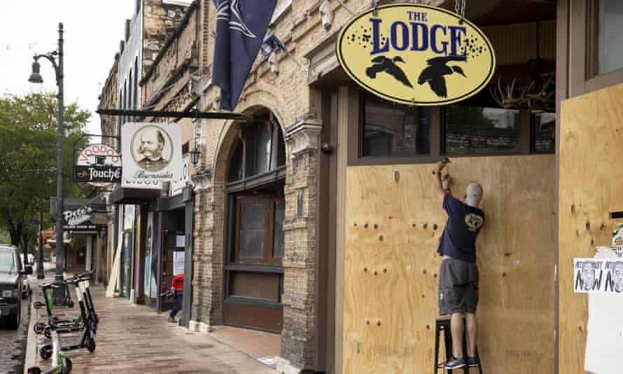 Matthew Gaskamp, general manager of The Lodge, boards up his bar on East 6th Street in Austin, Texas, Friday.
