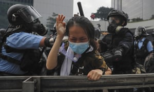 A protester reacts as she tackled by riot police during a massive demonstration outside the Legislative Council in Hong Kong.