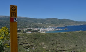 Signpost on one of the Andros Routes on the Greek island of Andros. Behind it is a small town by the sea shore.
