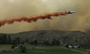 An air tanker drops red fire retardant on a wildfire near Twisp