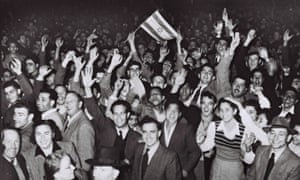 """(FILE) Israel At 60: The Birth Of A Nation<br>TEL AVIV, PALESTINE - NOVEMBER 29, 1947: Jubilant residents celebrate with what would become the Israeli flag after the United Nations decision to approve the partition of Palestine November 29, 1947 as crowds gather in front of the Mugrabi cinema in Tel Aviv in the British Mandate for Palestine. (Photo by Hans Pins/GPO via Getty Images)                      <eth>                                """"   <eth>"""